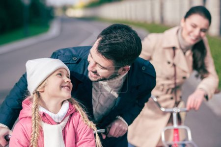 Photo for Happy family standing with bicycles and smiling at sunny autumn day - Royalty Free Image