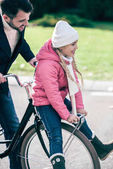 Father carrying smiling daughter on bicycle