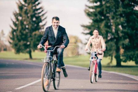 Foto de Familia feliz andar en bicicleta en el Parque otoño, padre llevando a su adorable hijita en bicicleta - Imagen libre de derechos