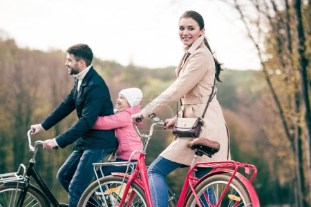 Photo for Happy family riding bicycles in autumn park, father carrying his adorable little daughter on bike - Royalty Free Image