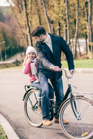 Father carrying daughter on bike