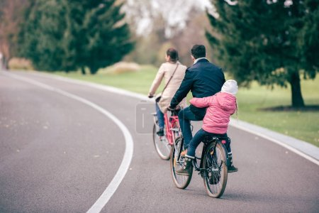 Photo for Back view of young family riding bicycles in autumn park, father carrying his daughter on bike - Royalty Free Image
