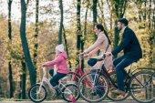 Happy family riding bikes in park