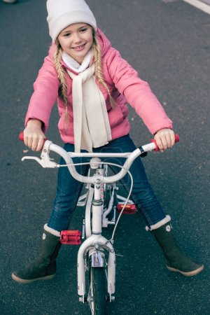Adorable smiling girl sitting on bicycle