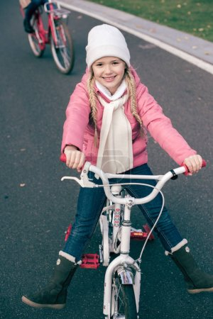Photo for Close-up portrait of adorable smiling little girl sitting on white bicycle on asphalt road - Royalty Free Image