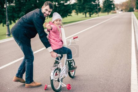 Father teaching daughter to ride bicycle