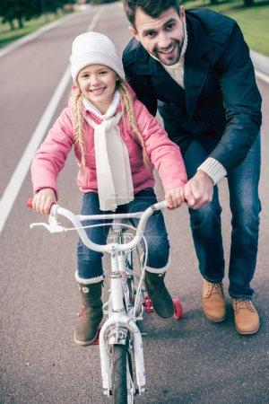 Foto de Feliz padre enseñando a su adorable hijita a andar en bicicleta en asfalto - Imagen libre de derechos
