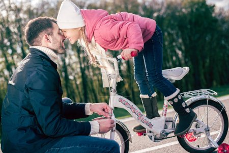 Father checking bicycle of little daughter