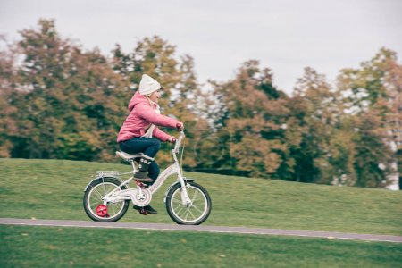 Little girl riding bicycle in park