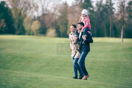 Happy family walking in autumn park