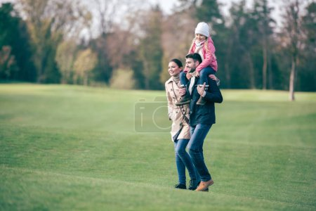 Photo for Happy family walking on green lawn in autumn park, father carrying his adorable little daughter on shoulders - Royalty Free Image