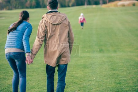 Photo for Back view of young man and woman holding hands and looking at their little child walking on green lawn - Royalty Free Image