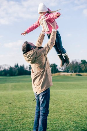 Father holding daughter and playing in park