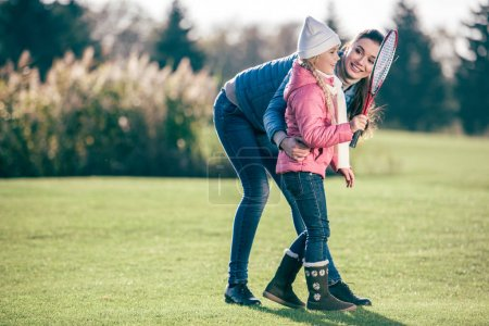 Smiling mother with daughter playing badminton