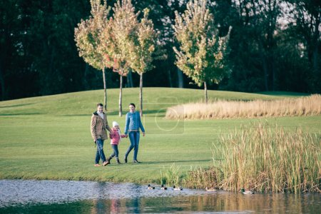 Photo for Happy family holding hands and walking near lake in autumn park - Royalty Free Image