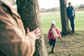 Parents playing hide-and-seek with daughter
