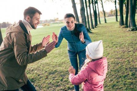 Photo pour Famille heureuse avec un enfant jouant et s'amusant dans le parc d'automne - image libre de droit