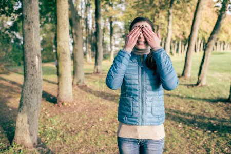 Photo for Front view portrait of beautiful young woman covering eyes with hands and standing in autumn park - Royalty Free Image