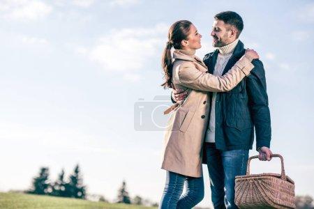 Photo pour Portrait de l'heureux couple debout embrassant avec panier de pique-nique sur la pelouse au jour de l'automne ensoleillé - image libre de droit