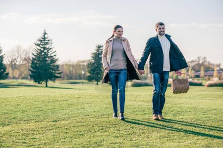 Happy couple walking with picnic basket