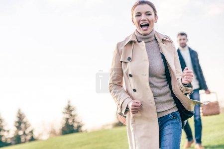 Photo pour Portrait de femme heureuse courant sur prairie verte et homme flou avec panier pique-nique debout - image libre de droit