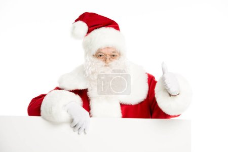 Photo for Santa Claus with blank white board, showing thumb up, isolated on white - Royalty Free Image