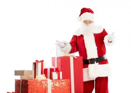 Photo pour Joyeux père Noël debout avec un tas de cadeaux de Noël isolé sur blanc - image libre de droit