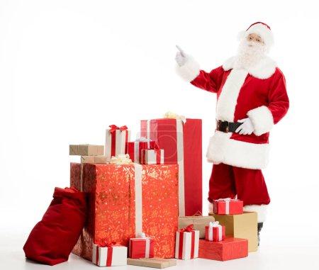 Photo pour Joyeux Père Noël debout avec une pile de cadeaux de Noël isolés sur blanc - image libre de droit