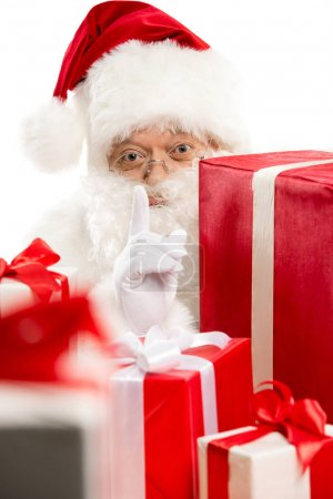 Santa Claus with pile of Christmas gifts