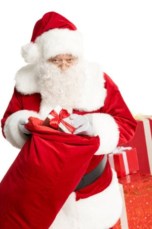 Santa Claus taking out Christmas gift from sack