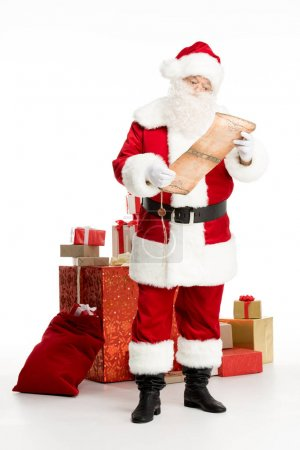 Photo for Happy Santa Claus standing near a pile of Christmas gifts and a big sack while reading wishlist - Royalty Free Image