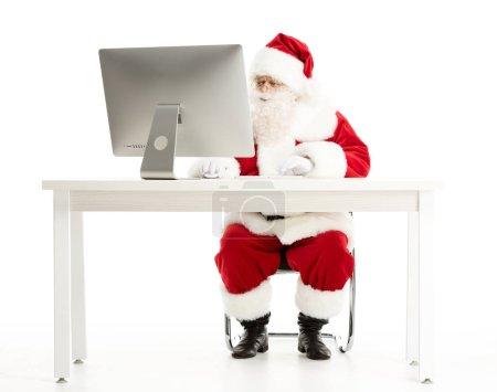 Serious Santa Claus looking at computer