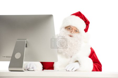 Santa Claus sitting at the desk with computer