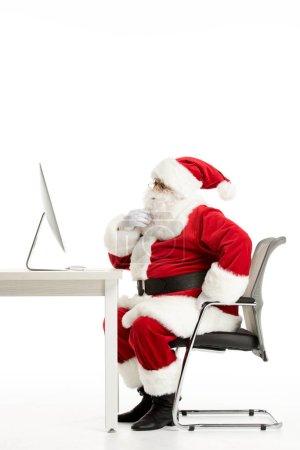 Photo pour Vue latérale du Père Noël réfléchi regardant l'ordinateur isolé sur blanc - image libre de droit
