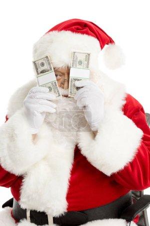 Santa Claus peeking from dollar banknotes