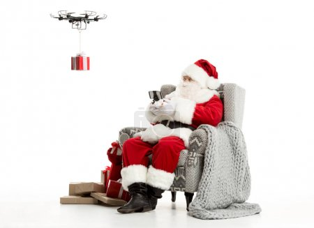 Photo for Santa Claus, sitting on grey armchair, using hexacopter drone - Royalty Free Image