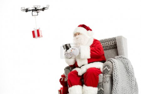 Photo for Santa Clau, sitting on grey armchair, using hexacopter drone - Royalty Free Image