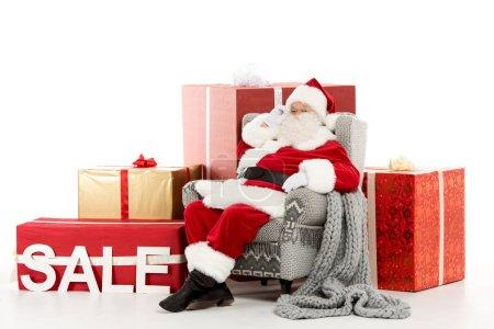 Photo pour Père Noël assis sur un fauteuil gris avec signe de vente et boîtes-cadeaux derrière isolé sur blanc - image libre de droit