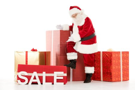 Photo for Happy Santa Claus standing near a pile of Christmas gifts with and pointing on Sale sign - Royalty Free Image