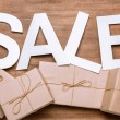 Sale sign with gift boxes on wooden surface
