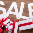 Sale sign with gift boxes on wooden surface...