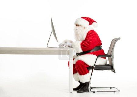 Photo pour Vue latérale du Père Noël à l'aide d'un ordinateur assis au bureau isolé sur blanc - image libre de droit