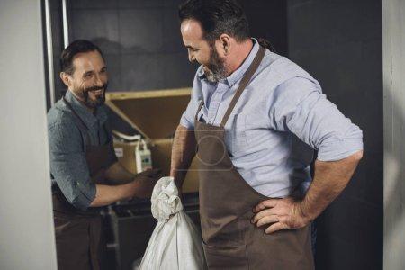 Photo pour Sourire des travailleurs de sexe masculin en tabliers avec sac de grains à la brasserie - image libre de droit