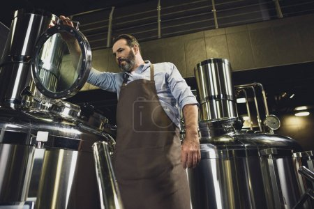 Male brewer in apron inspecting tank at the brewer...