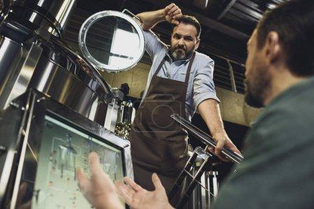 Photo pour Brasseurs mâles tabliers travaille avec réservoirs et équipements technologiques à la brasserie - image libre de droit