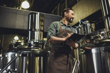 Worker inspecting equipment at brewery