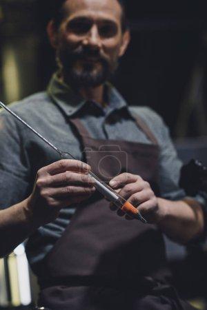 Photo pour Souriant travailleur brasserie en tablier tenant le thermomètre industriel - image libre de droit