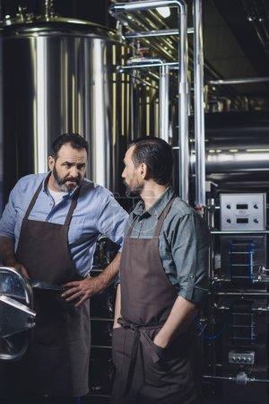 Photo pour Travailleurs masculins brasserie tabliers parler et regarder les uns les autres - image libre de droit
