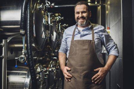 Photo pour Travailleur souriant de brasserie en tablier regardant la caméra - image libre de droit