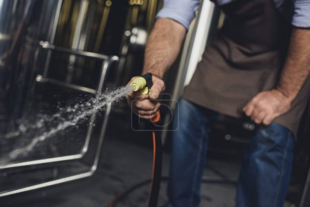 Worker cleaning brewery equipment